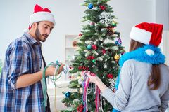 The young family decorating christmas tree on happy occasion Royalty Free Stock Photos