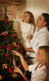 Young family decorating the Christmas tree Stock Images