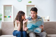 The young family discussing travel plans with map Royalty Free Stock Photos