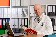 Young family doctor in his office. Reading a book Royalty Free Stock Images
