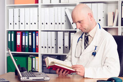 Young family doctor in his office. Reading a book Royalty Free Stock Image