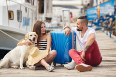 Young family with a dog preparing for the journey. A young married couple,a men with a beard and a pregnant woman,brunette,long straight hair, with a friend,a Royalty Free Stock Photo