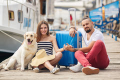 Young family with a dog preparing for the journey. A young married couple,a men with a beard and a pregnant woman,brunette,long straight hair, with a friend,a Royalty Free Stock Image