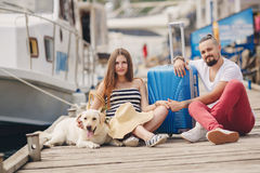 Young family with a dog preparing for the journey. A young married couple,a men with a beard and a pregnant woman,brunette,long straight hair, with a friend,a Stock Image