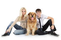 A young family with a dog sitting on floor Royalty Free Stock Photography