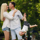 A young family and a dog walking in a city park. Stock Photography