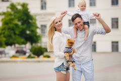 A young family and a dog walking in a city park. Royalty Free Stock Images