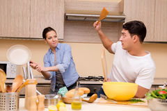 The young family doing funny fight at kitchen. Young family doing funny fight at kitchen royalty free stock photo