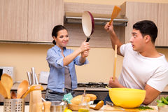 The young family doing funny fight at kitchen Stock Image