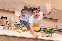 The young family doing funny fight at kitchen. Young family doing funny fight at kitchen royalty free stock images