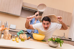 The young family doing funny fight at kitchen. Young family doing funny fight at kitchen royalty free stock photography