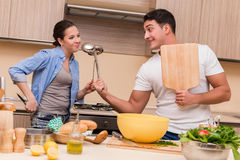 The young family doing funny fight at kitchen. Young family doing funny fight at kitchen royalty free stock photos