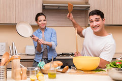 The young family doing funny fight at kitchen. Young family doing funny fight at kitchen stock photos
