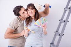The young family doing renovation at home  - painting walls Royalty Free Stock Photography