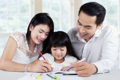 Young family doing schoolwork together Stock Image