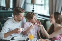 Young family eating indoors. Young family eating in a restaurant Stock Image