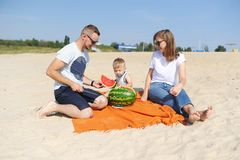 Young family is eating a watermelon together on the sandy beach royalty free stock photos