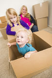 Young Family In Empty Room Playing With Moving Boxes Royalty Free Stock Images