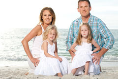 Young family enjoy sunny day at the beach. Royalty Free Stock Photography