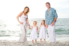 Young family enjoy sunny day at the beach. Royalty Free Stock Image
