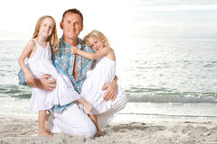 Young family enjoy sunny day at the beach. Stock Photos