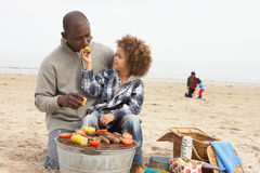 Young Family Enjoying Barbeque On Beach royalty free stock photography