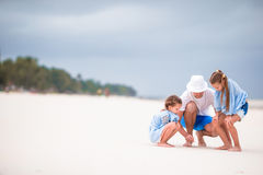 Young family enjoying beach summer vacation. Kids and dad find something on the sand. Happy beautiful family on a beach during summer vacation Royalty Free Stock Photos