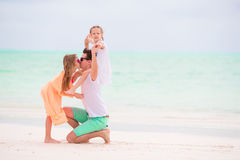 Young family enjoying beach summer vacation. Kids and dad find something on the sand. Happy beautiful family on a beach during summer vacation Royalty Free Stock Photography