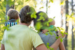 Young family enjoying a beautiful sunny day outdoors in a green Royalty Free Stock Images