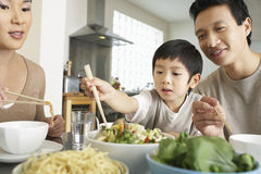 Young Family Enjoying Meal. Young parents watching son trying to use chopsticks at dining table Royalty Free Stock Photos
