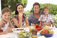 Young Family Enjoying Outdoor Meal Together Stock Image