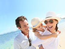 Young family enjoying their summer holidays on the beach Stock Photos