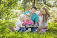Young Family Enjoys Reading a Book in the Park Royalty Free Stock Photo