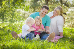 Young Family Enjoys Reading a Book in the Park Royalty Free Stock Photography