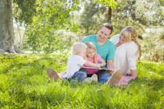 Young Family Enjoys Reading a Book in the Park Royalty Free Stock Image