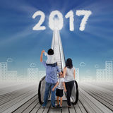 Young family with escalator and number 2017 Stock Photo