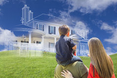 Young Family Facing Ghosted House Drawing Behind. Young Family Facing Ghosted House Drawing, Partial Photo and Rolling Green Hills Royalty Free Stock Image
