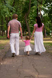 A young family, father, mother and toddler daughter walking in t Stock Photos