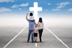 Young family follow a cross on the road Stock Photo