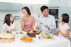 Young family of four enjoying healthy meal in kitchen Royalty Free Stock Image