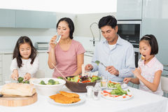 Young family of four enjoying healthy meal in kitchen Stock Photo