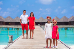 Young family of four have fun on wooden jetty Royalty Free Stock Photos