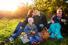 Happy young family of four having picnic at meadow at summer day royalty free stock photo