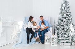 Young family of four near decorated Christmas fir-tree in white room stock photography