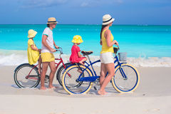 Young family of four riding bicycles on a tropical sand beach Royalty Free Stock Image