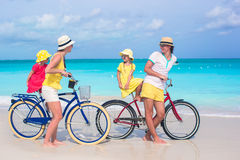 Young family of four riding bicycles on a tropical sand beach Stock Image