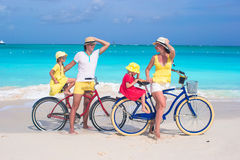 Young family of four riding bicycles on tropical Stock Photos