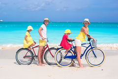Young family of four riding bicycles on tropical Stock Images