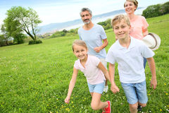 Young family of four running on green grass Stock Photography
