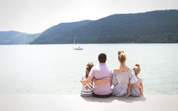 Young family of four sitting by lake Stock Photo